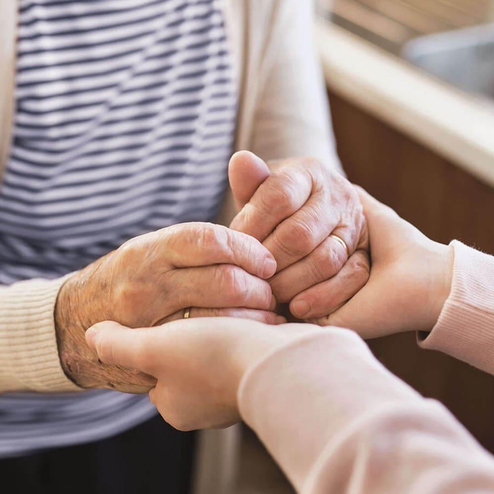 Senior holding hands with a caretaker at Anthology of Farmington Hills in Farmington Hills, Michigan