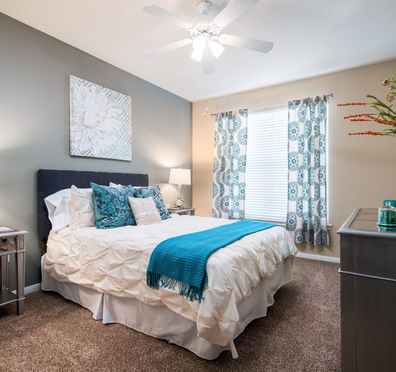 Well-furnished master bedroom with an accent wall and a ceiling fan in a model home at Reserve at Pebble Creek in Plano, Texas
