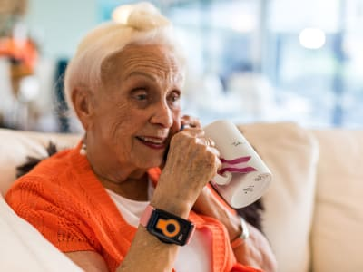 Woman wearing CarePredict drinking coffee at