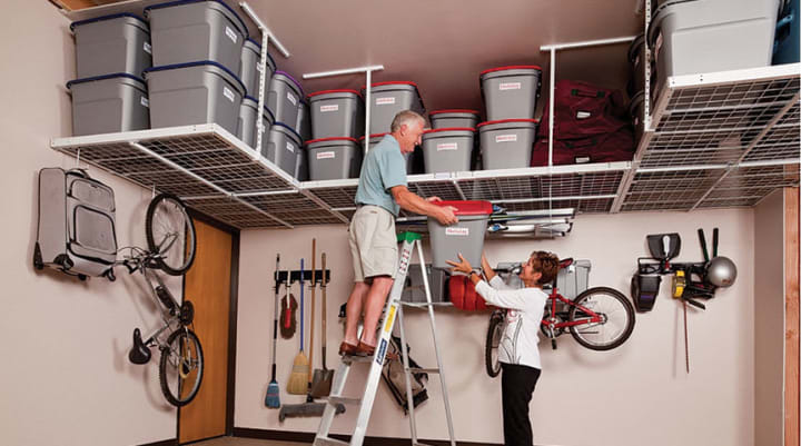 decluttering garage tip - couple using overhead garage storage