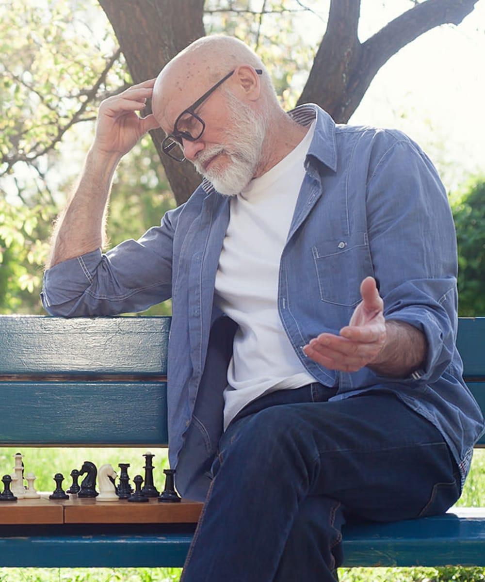 Senior playing chess in the park at Kirkwood Orange in Orange, California