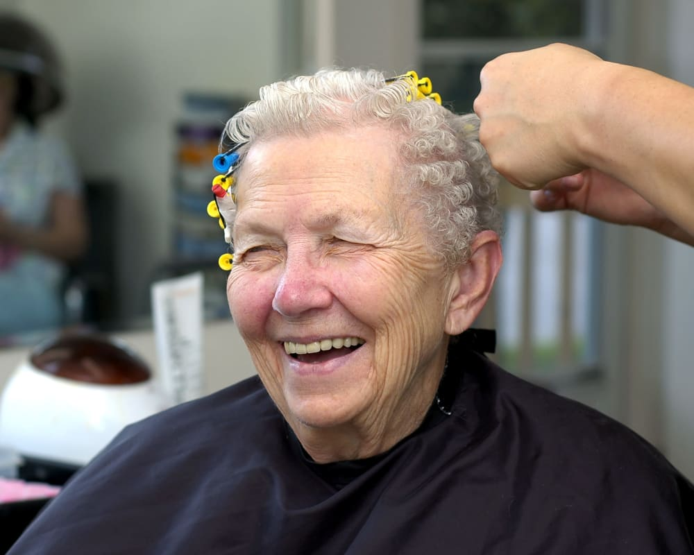 A resident having her hair curled at Welbrook Grand Montecito in Las Vegas, Nevada