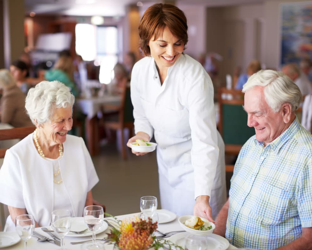 Two residents being served a meal at Western Slope Memory Care in Grand Junction, Colorado