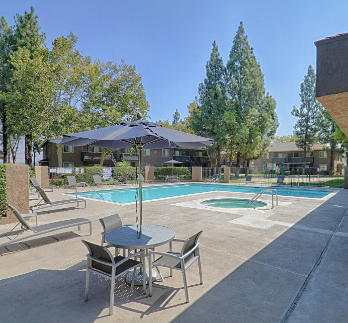 Pool and spa area on a beautiful day at Creekside Village Apartment Homes in San Bernardino, CA