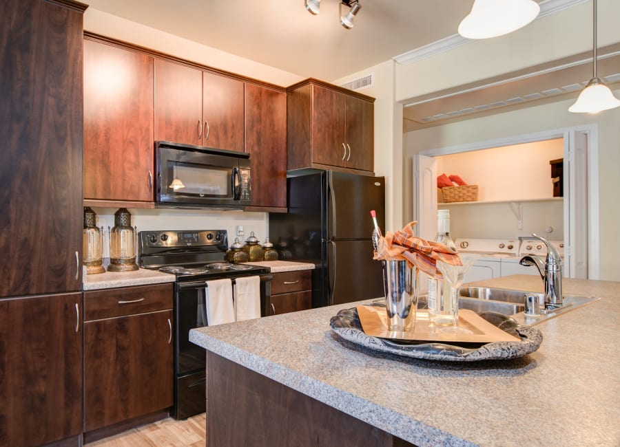 Gourmet kitchen with granite countertops and rich, dark wood cabinetry in a model home at Broadstone Towne Center in Albuquerque, New Mexico