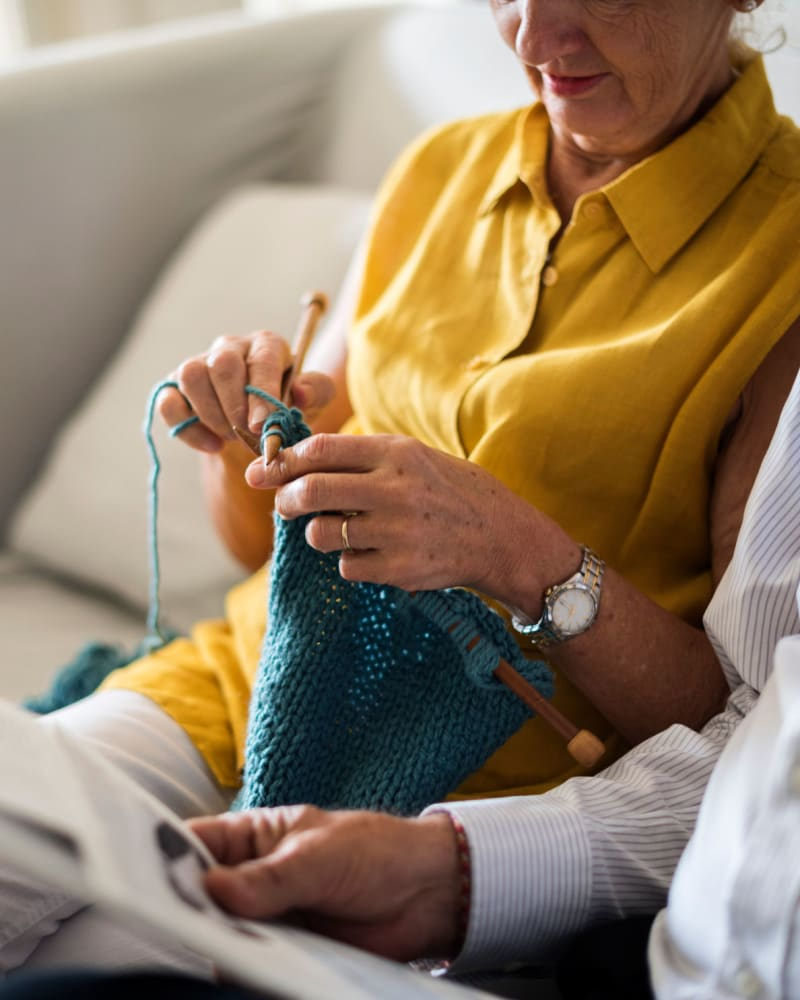 Resident knitting on the couch at Villa at the Lake in Conneaut, Ohio