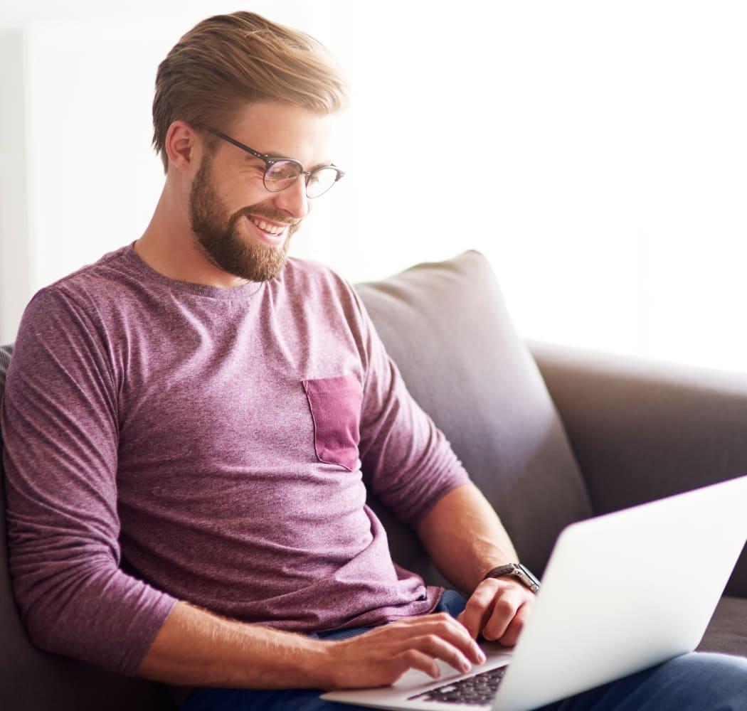 Man reading from his personal computer at Tammaron Village Apartments in Oklahoma City, Oklahoma