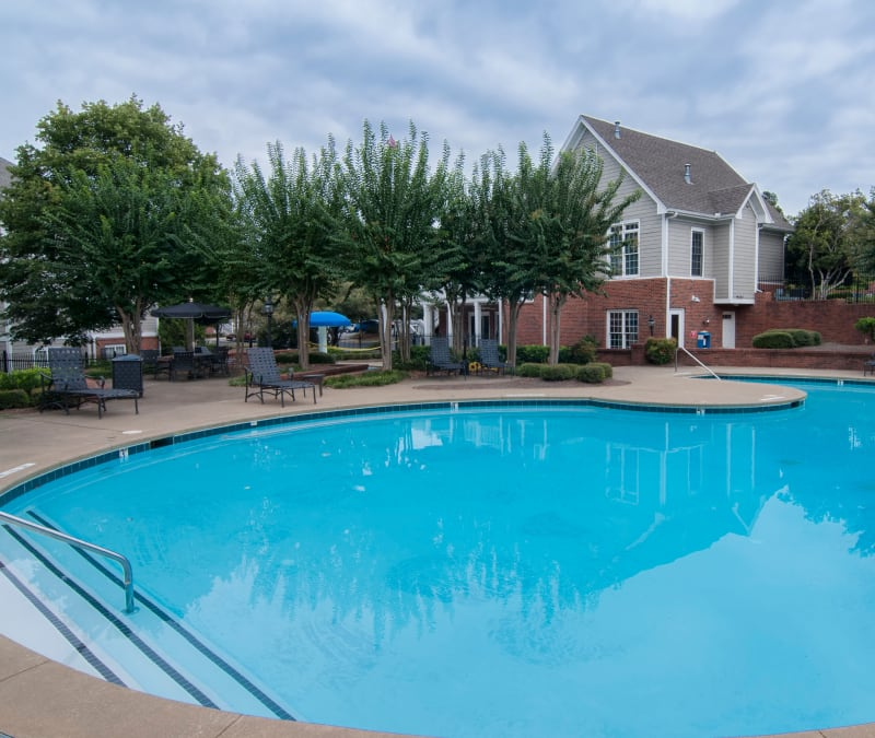 Swimming pool area with chaise lounge chairs nearby at Bellingham Apartment Homes in Marietta, Georgia