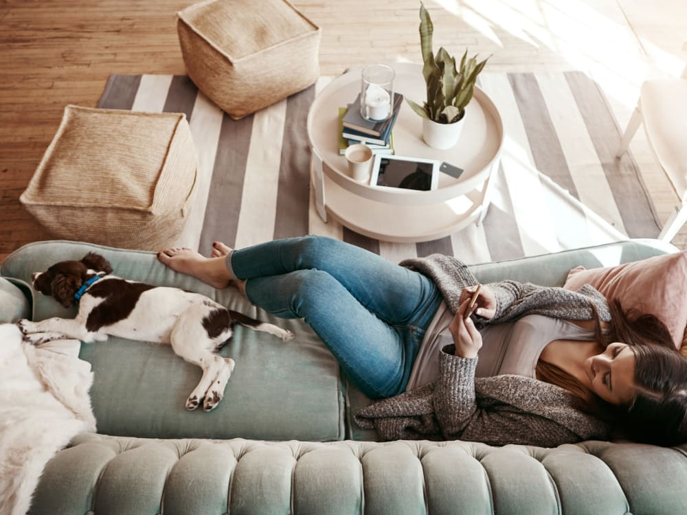 Resident and her pup relaxing on the couch in their new home at TwentyTwenty Apartments in Portland, Oregon