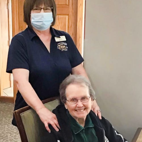 Masked caretaker with a resident at Glen Carr House Memory Care in Derby, Kansas