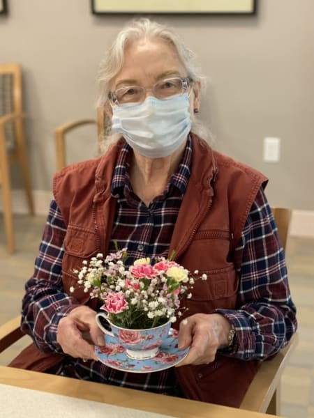 A resident at Monterey shows off her teacup bouquet