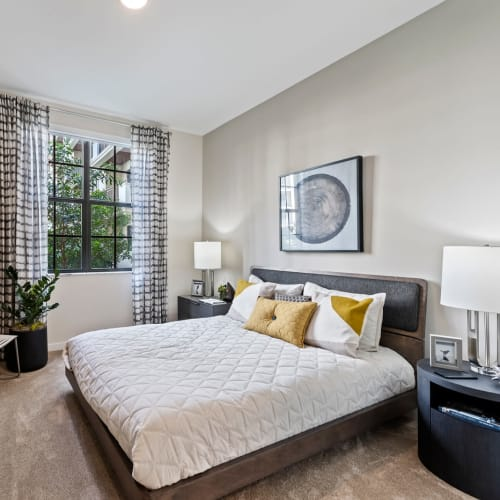 Model bedroom with carpet and cute side tables at 6600 Main in Miami Lakes, Florida