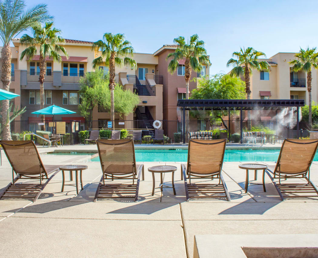 Chaise lounge chairs next to the pool at The Residences at Stadium Village in Surprise, Arizona