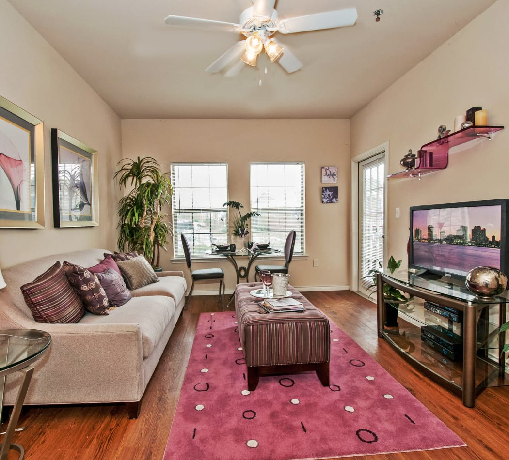 Open-concept living area with ceiling fan and hardwood floors in model home at Trails at Buda Ranch in Buda, Texas