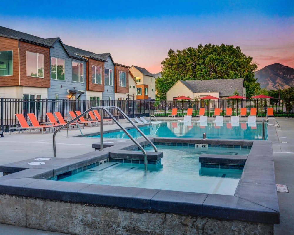 Luxury swimming pool with a sundeck and lounge chairs at Hawthorne Townhomes in South Salt Lake, Utah