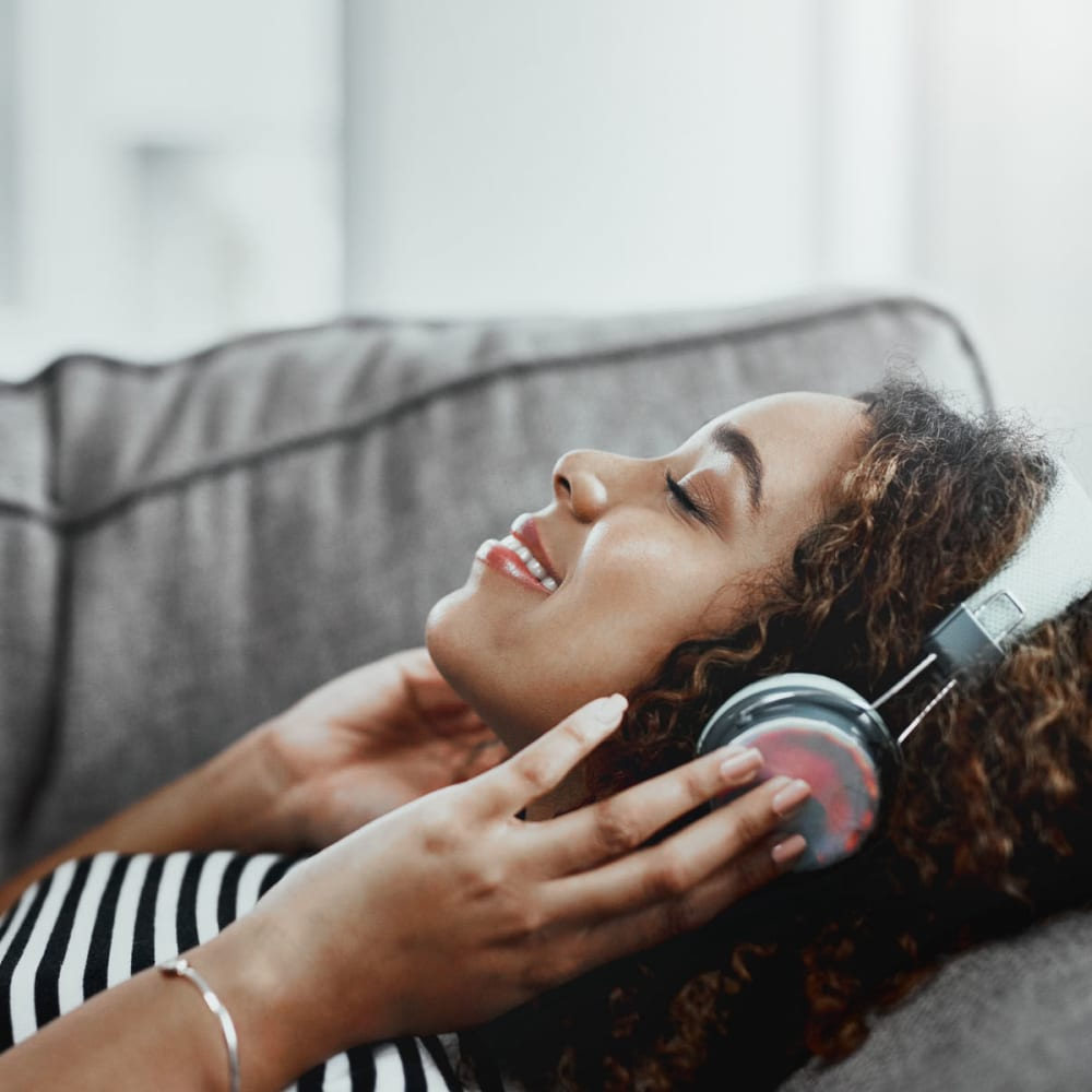 Resident jamming to some tunes on headphones from the comfort of her couch at Oaks Estates of Coppell in Coppell, Texas