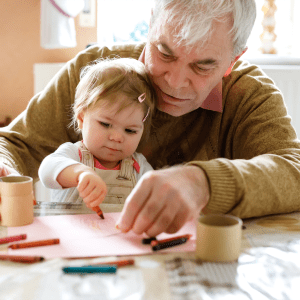 Resident painting with his young grandchild at Sunstone Village in Denton, Texas
