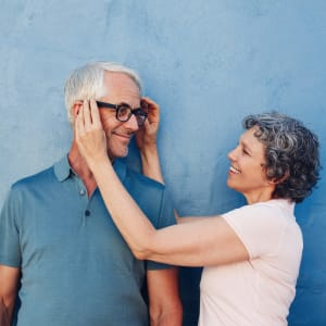 Resident couple standing against a blue wall outside at Sunstone Village in Denton, Texas