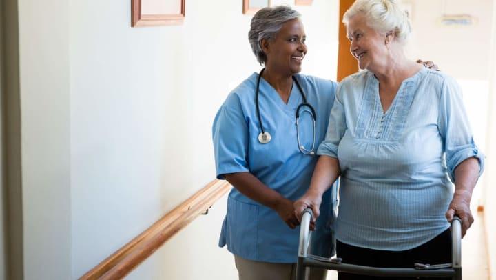 Caregiver assisting senior on walker