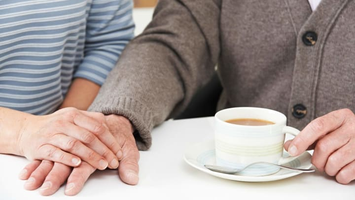 Senior man holding hands with adult daughter