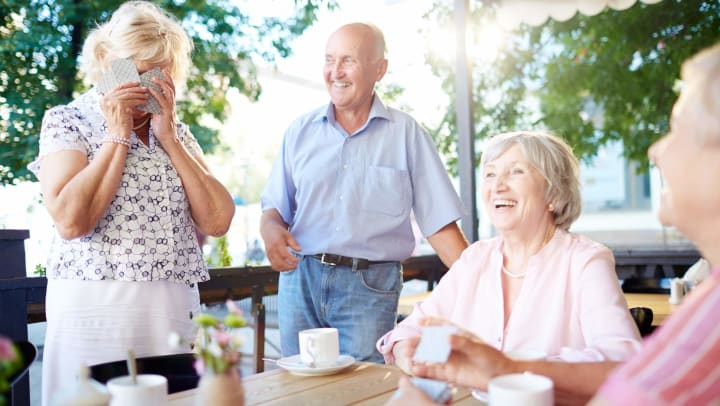 Senior woman covered face with cards as others laugh along