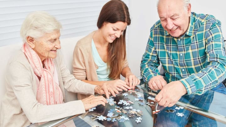 Seniors completing jigsaw puzzle with adult daughter
