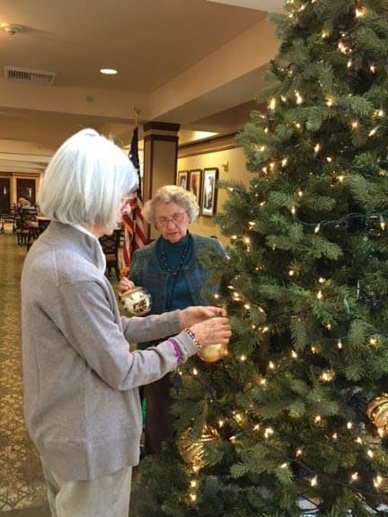 Merrill Gardens at The University decorating the tree together with gold ornaments