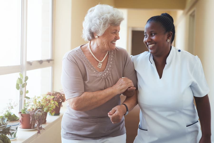 A resident walking with a CNA at Americare Senior Living