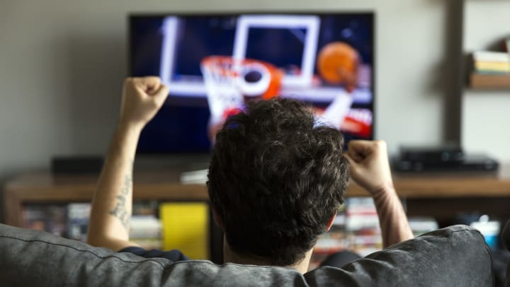A man on a couch cheering. Basketball playing on the TV in front of him.