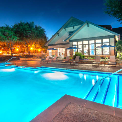 Swimming pool illuminated by underwater lights at dusk at Olympus Town Center in Keller, Texas