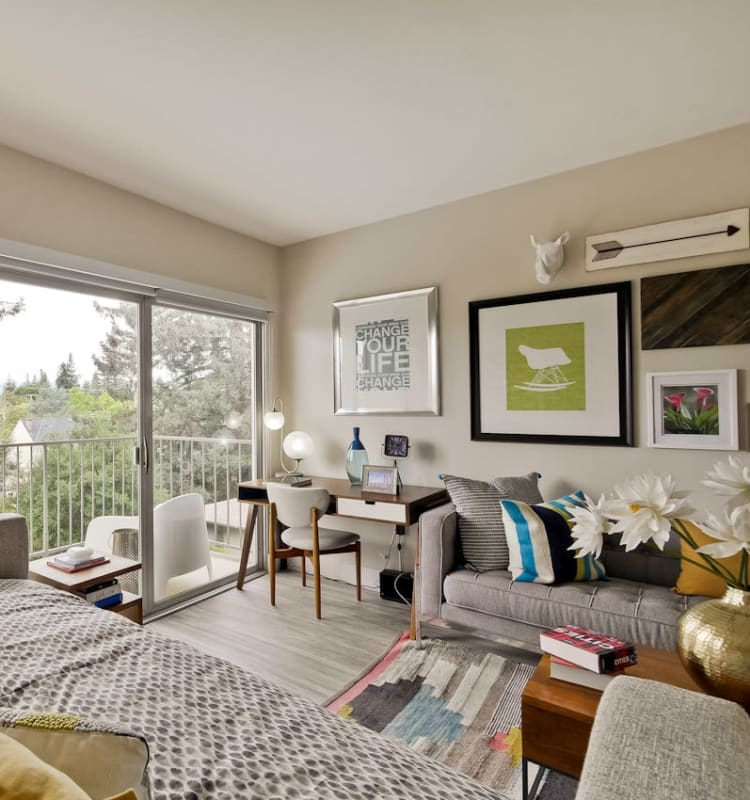 Living area looking out on the spacious private balcony outside a model home at Mia in Palo Alto, California