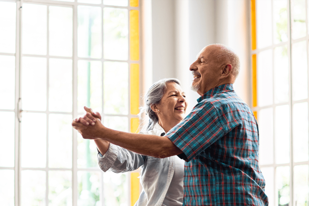 Two residents dancing in a brightly lit lounge at Sunstone Village in Denton, Texas