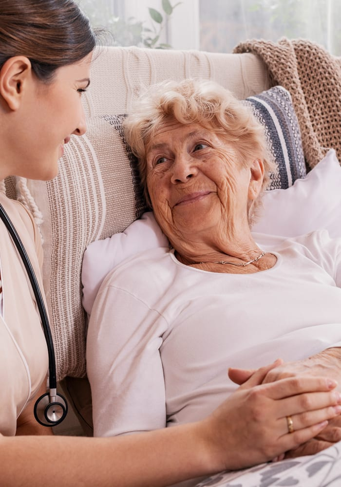 A caregiver attends to a woman in her apartment at The Renaissance of Stillwater in Stillwater, Oklahoma