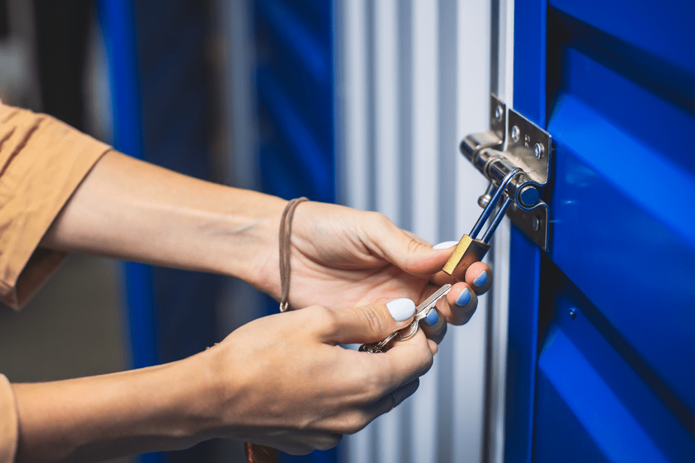 Closing the padlock on a blue storage unit door at Airport Road Storage in Monterey, California