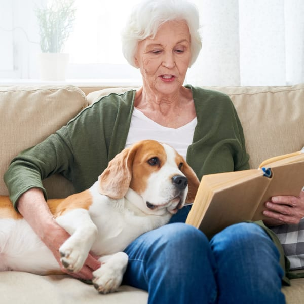A resident reading to her dog at Chesapeake Place Senior Living in Chesapeake, Virginia.