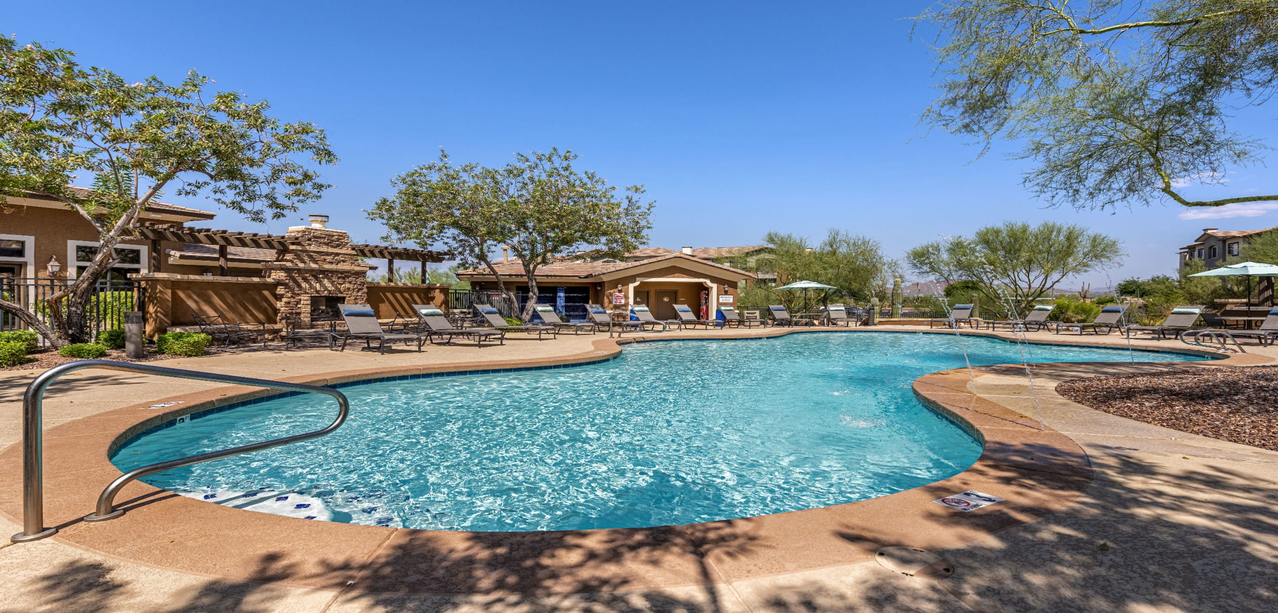 Sparkling resort style pool with water features surrounded by lounge chairs at Marquis at Sonoran Preserve in Phoenix Arizona,