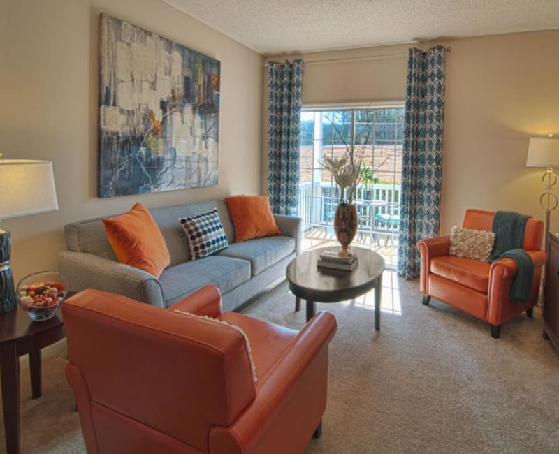Living room with plush carpeting at Amber Chase Apartment Homes in McDonough, Georgia