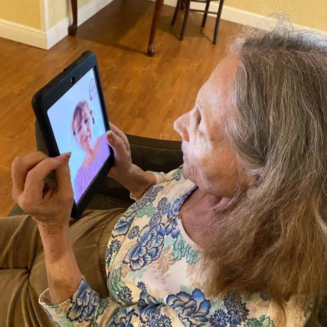 Resident video chatting relative at Grand Villa of Melbourne in Melbourne, Florida