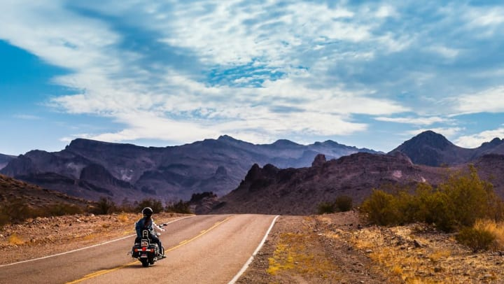 Motorcyclist traveling down Route 66 near Olympus Encantata in Albuquerque, New Mexico