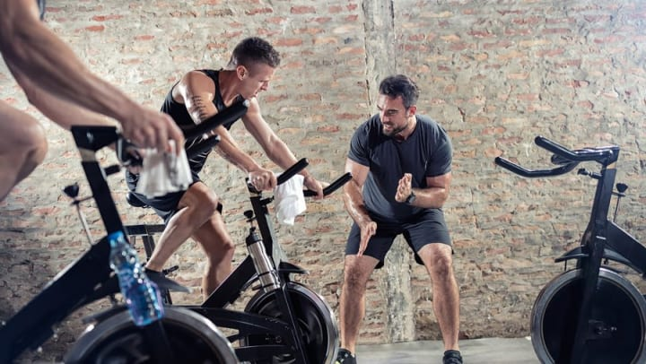 Trainer with pupil during a spinning class at a gym near Olympus 7th Street Station in Fort Worth, Texas