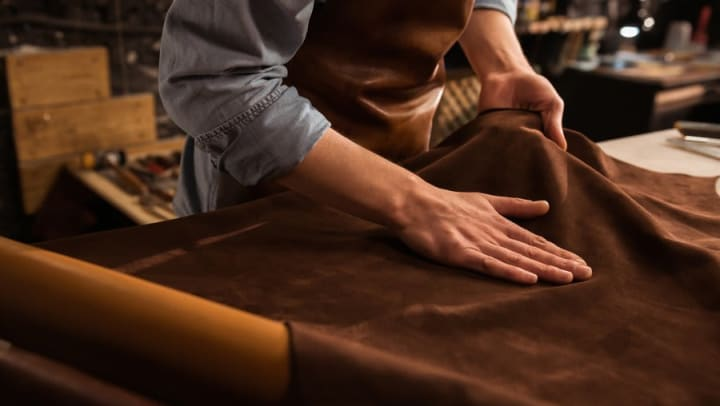 Leatherworker preparing fabric for upholstering near Olympus Fenwick in Savannah, Georgia