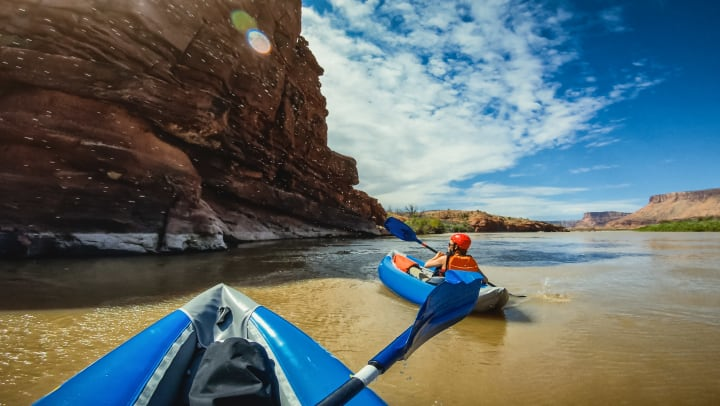 View from perspective of a kayaker of another kayaker on the shore of a -river.