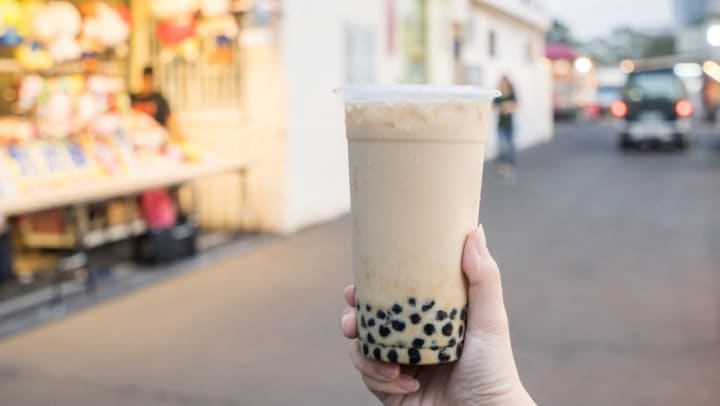 Plastic cup of boba tea near Lux on Main in Carrolton, Texas