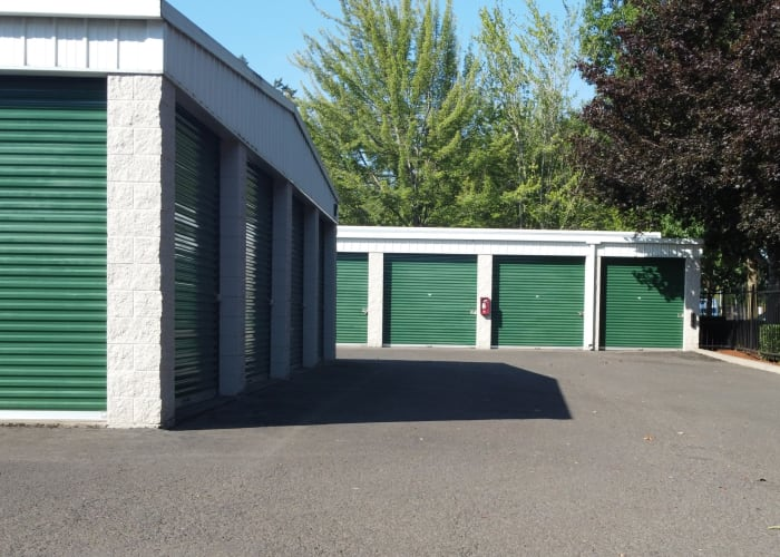 Outdoor storage units with green doors and wide driveways at A Storage Place in Tualatin, Oregon