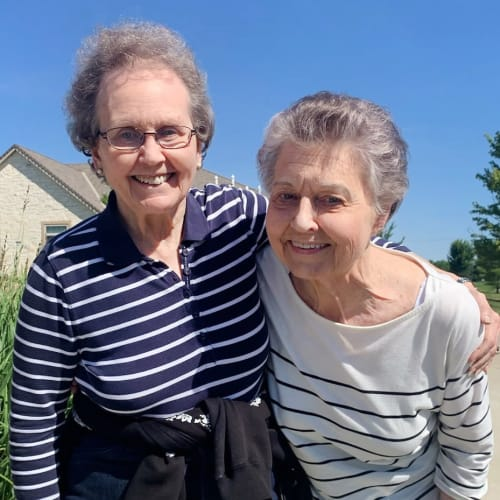 Resident friends taking a walk at Glen Carr House Memory Care in Derby, Kansas