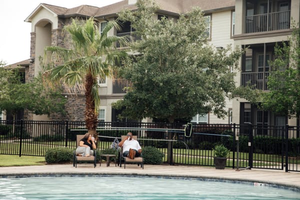 Two people laughing poolside at Belmere Luxury Apartments in Houma, LA together.