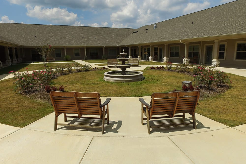 View of benches and courtyard at The Claiborne at Hattiesburg Assisted Living in Hattiesburg, Mississippi