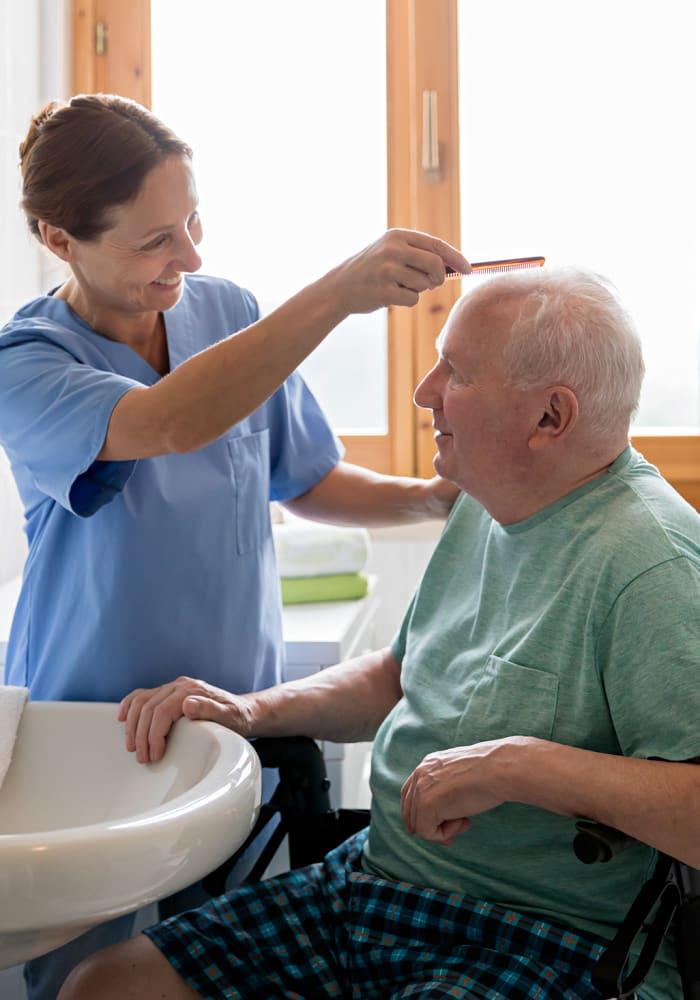 A nurse at Cascade Valley Senior Living in Arlington, Washington helps a resident comb his hair