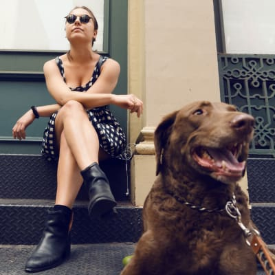 A women hanging out with her dog on the front steps at 210-220 E. 22nd Street in New York, New York