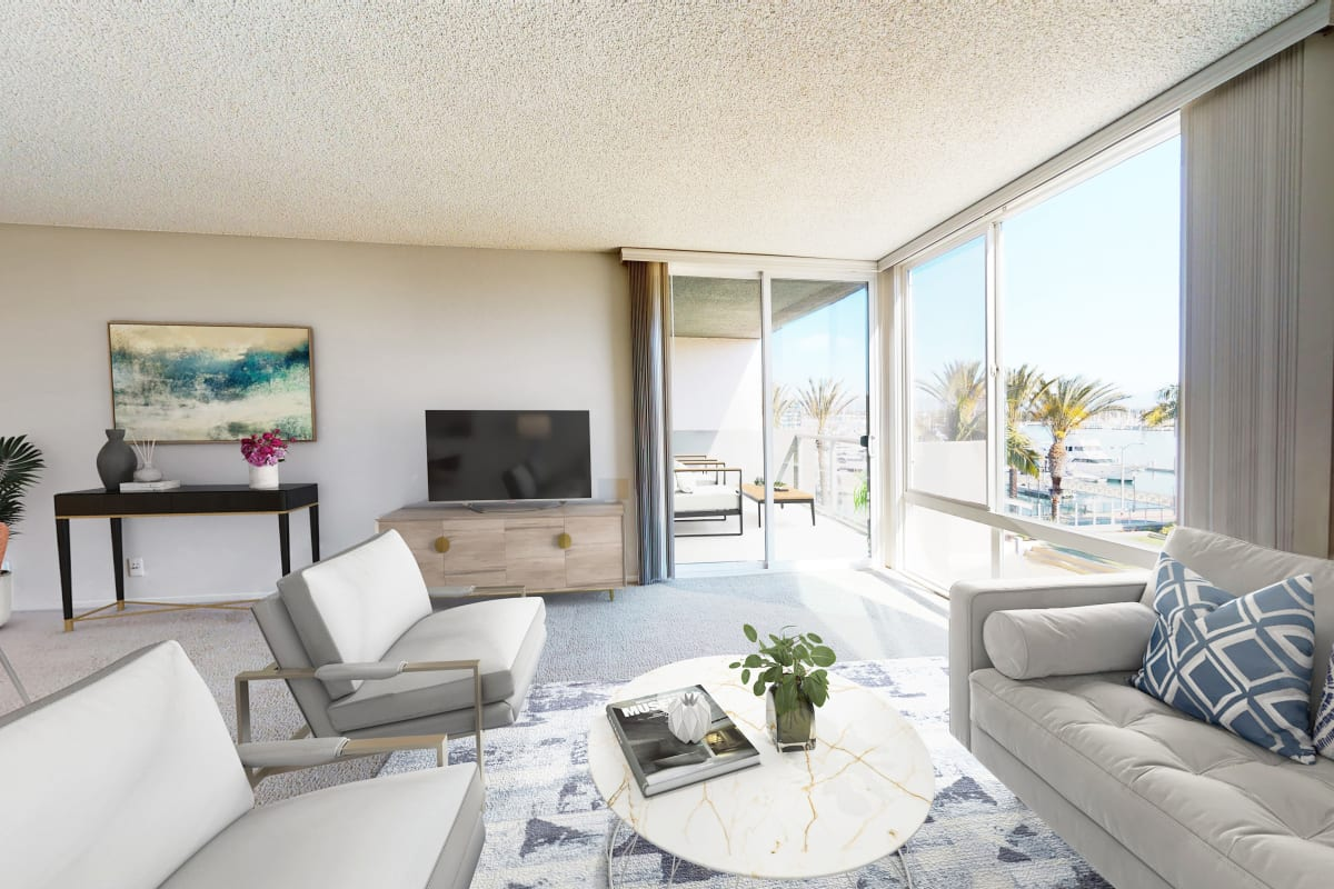 Open-concept living room with floor-to-ceiling windows and views of the marina at Waters Edge at Marina Harbor in Marina del Rey, California